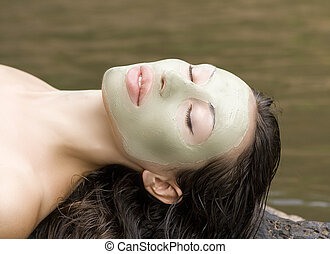 Woman with clay facial mask in beauty spa Outdoor - Spa...