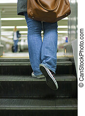 Escalator with view of young woman feet