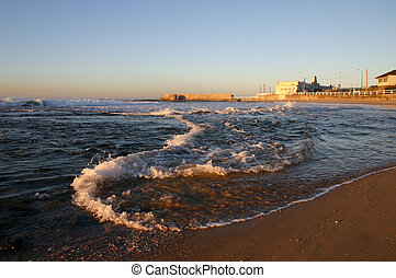 A wave rolls along the shore as the tide comes in on a...