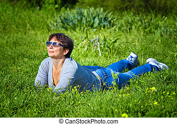 Portrait of a mature woman - middle aged woman lying on a...
