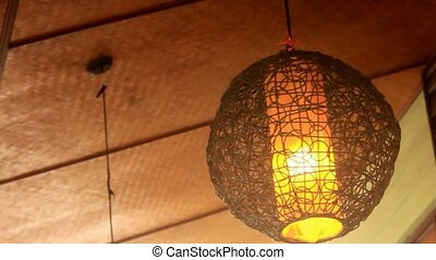 wicker round lantern hanging and swaying in wind at cafe -...
