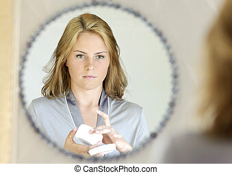 Beautiful young woman applying face cream in front of mirror