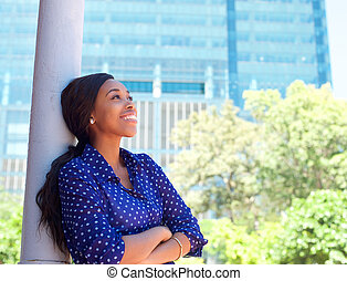 Friendly smiling business woman outside office building -...