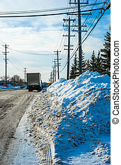 Roadside after snow clearing - Windrow of snow on city...
