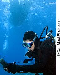 Scuba Diver Checking Gauges under the Boat - Female Scuba...