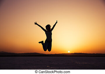 Happy in vacation - silhouette of happy woman jumping in...