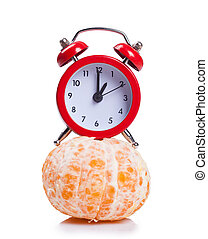 Alarm clock and orange fruit