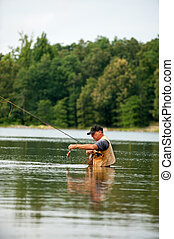 Fly Fishing - Man fly fishing in calm water