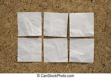six blank white reminder notes on cork board