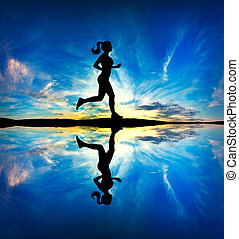 Woman running at the beach - Silhouette of a Fitness Girl...