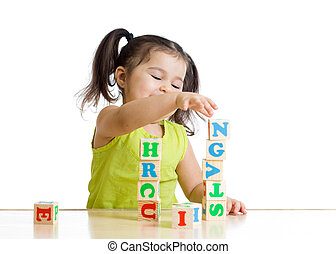 Little girl playing with wooden blocks with letters