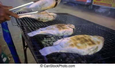 Grilled Tilapia fish in street market of Thailand. Koh Samui...