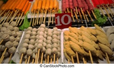 Street food in Thailand - fried sausages, meatballs and...