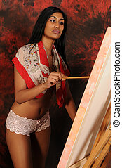 Painter - Beautiful young Indian woman working on a canvas
