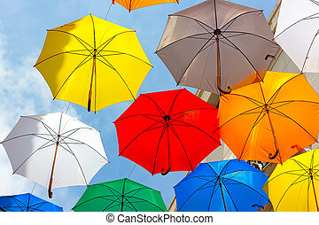 Colorful umbrellas against the sky in city settings....