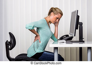 woman with back pain in the office - a woman sitting at a...
