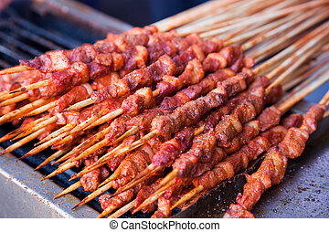 Roasted meat on wood sticks prepared for eating