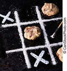 Chocolate chip cookies on noughts and crosses sugar grid,...