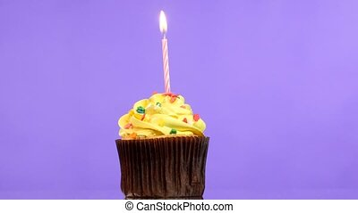 tasty birthday cupcake with one candle, on purple background...