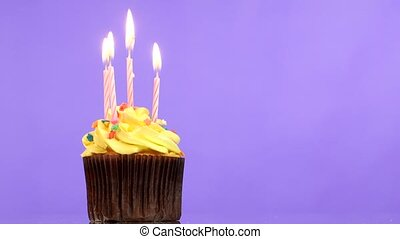 tasty birthday cupcake with four candle, on purple...