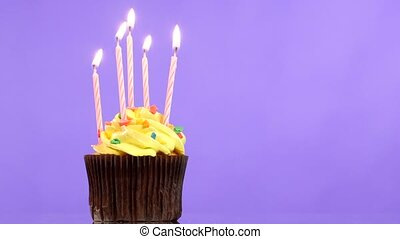 tasty birthday cupcake with five candle, on purple...