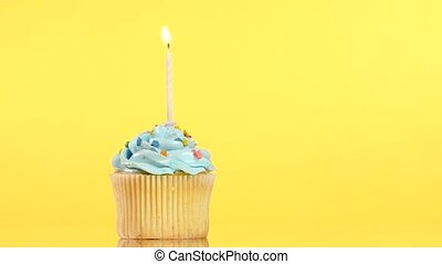 tasty birthday cupcake with one candle, on yellow background...