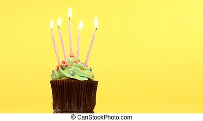 tasty birthday cupcake with five candle, on yellow...