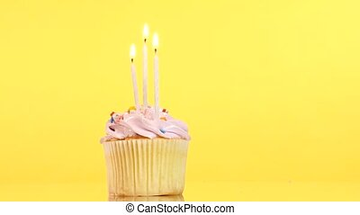 tasty birthday cupcake with three candle, on yellow...