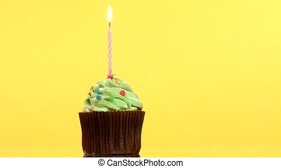 tasty birthday cupcake with one candle, on yellow...