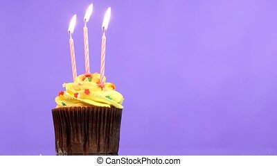 tasty birthday cupcake with three candle, on purple...