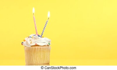 tasty birthday cupcake with two candle, on yellow background...