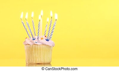 tasty birthday cupcake with nine candle, on yellow...