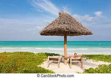 Woman sunbathing on tropical beach. - Women sunbathing on...