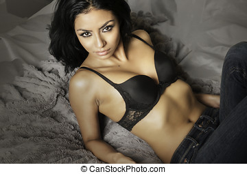 Beautiful exotic young woman lying on bed
