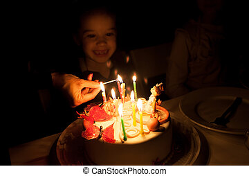 Little girl blowing out candles on birthday cake - Little...