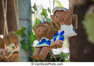 Clay doll on a swing