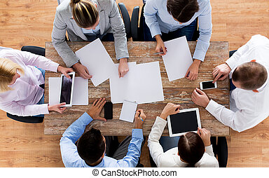 close up of business team with papers and gadgets