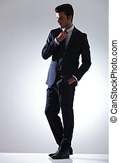 handsome business man fixing hid tie. - Side view picture of...