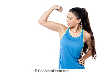 Sporty woman flexing her biceps - Fitness woman looking at...