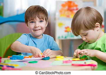 children making by hands - kids boys with play clay toys at...