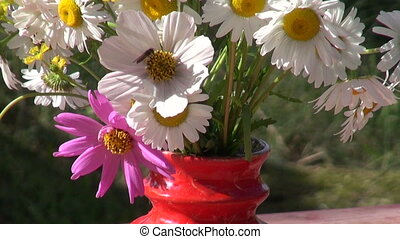 red vase with flowers on table in summer farm yard