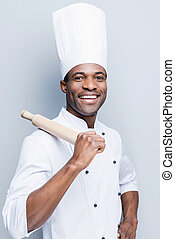 He is a champion in the kitchen. Cheerful young African chef in white uniform carrying rolling pin on his shoulder while standing against grey background