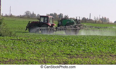 Tractor spray fertilize crop field - Tractor spray fertilize...