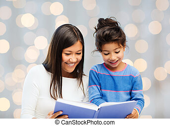 happy mother and little daughter reading book - family,...