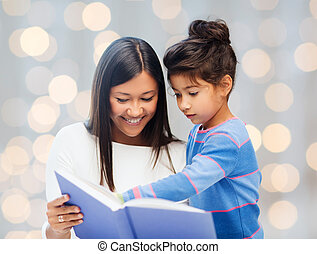 happy mother and daughter reading book - family, children,...
