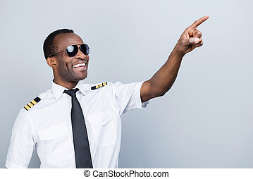 In love with sky. Cheerful African pilot in uniform pointing...