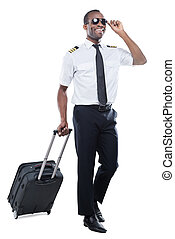 Ready to new flight. Happy African pilot in uniform walking and carrying suitcase while being isolated on white background