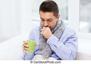 ill man with flu drinking tea and coughing at home -...