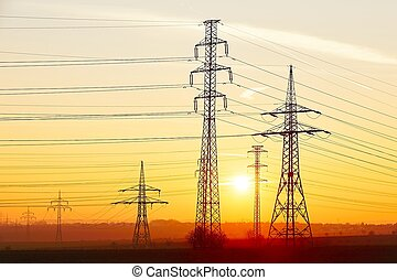 Electricity pylons - Silhouette electricity pylons during...