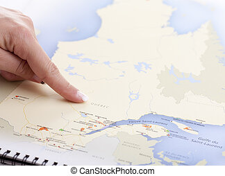 A hand who pointing Quebec on a MAP